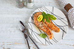 Grilled Salmon steak with lemon and herbs. Grilled Salmon steak with lemon and herbs on white dish. Healthy food concept Stock Photos