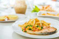 Grilled salmon steak meal served with salad Stock Photos