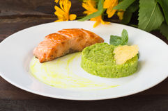 Grilled salmon steak with pea puree, cheese crisps and basil on a plate the sauce. Wooden rustic background. Close-up royalty free stock photography