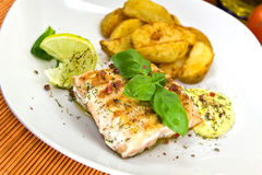 Grilled salmon steak with potato wedges.  stock image