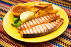 Grilled salmon steak with potatoes and sauce Stock Images