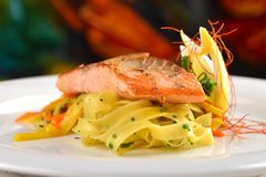 Grilled salmon steak on ribbon pasta. And lemon royalty free stock image