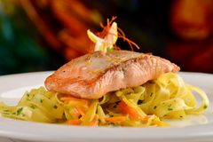 Grilled salmon steak on ribbon pasta Stock Photography