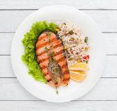 Grilled salmon steak and risotto on garnish. Top view. Healthy food, delicacy, lunch dish concept. White wooden planks background Royalty Free Stock Images