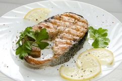 Grilled salmon steak on  round white plate Royalty Free Stock Photo