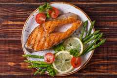 Grilled salmon steak served with asparagus, tomato and lemon. stock images