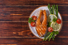 Grilled salmon steak served with asparagus, tomato and lemon. stock image