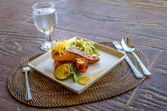Grilled salmon steak served with pasta and vegetables in a small Royalty Free Stock Photo