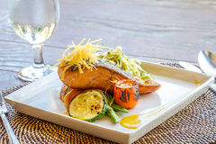 Grilled salmon steak served with pasta and vegetables in a small Royalty Free Stock Image