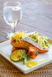 Grilled salmon steak served with pasta and vegetables in a small Stock Photography