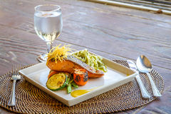 Grilled salmon steak served with pasta and vegetables in a small Stock Photos