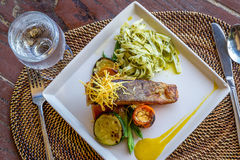 Grilled salmon steak served with pasta and vegetables in a small Royalty Free Stock Photography