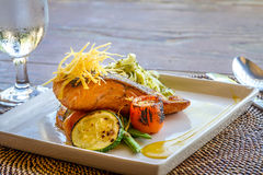 Grilled salmon steak served with pasta and vegetables in a small Royalty Free Stock Photos