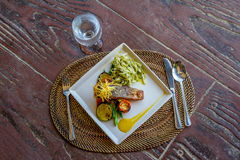 Grilled salmon steak served with pasta and vegetables in a small Royalty Free Stock Images