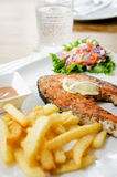 Grilled salmon steak served with salad, chips, Royalty Free Stock Photos