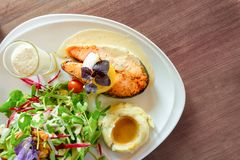 Grilled salmon steak sliced on white plate with mixed vegetable salad, mashed potatoes and topping in a glass, food in a dish stock image