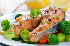 Grilled salmon steak. Tasty grilled salmon steak on mixed colorful vegetables, lemons and a fishing net in the background stock photo