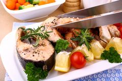 Grilled salmon steak and vegetables with grill tongs Stock Image