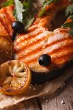 Grilled salmon steak and vegetables macro on paper. Vertical Stock Images