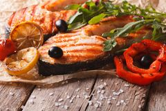 Grilled salmon steak and vegetables on an old table. Horizontal Stock Image