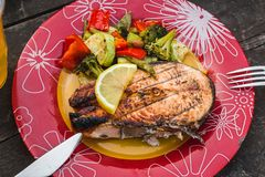 Grilled salmon steak with vegetables on plate stock photo