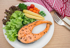 Grilled salmon steak with vegetables on plate Stock Images