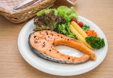 Grilled salmon steak with vegetables on plate Stock Photography