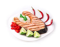 Grilled salmon steak with vegetables on plate. Stock Photos