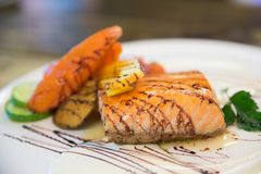 Grilled salmon steak and vegetables in white dish at Japanese fo Royalty Free Stock Image