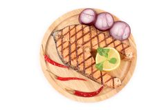 Grilled salmon steak on wooden platter. Stock Photos