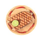 Grilled salmon steak on wooden platter. Royalty Free Stock Image
