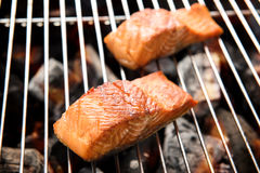 Grilled salmon steaks on the flaming royalty free stock image