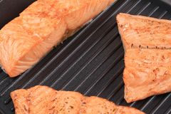 Grilled salmon steaks on frying pan. Royalty Free Stock Photos