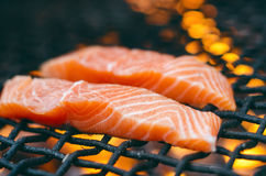 Grilled salmon steaks on a grill. Fire flame grill. Restaurant and garden kitchen. Garden party. Healthy dish. Grilled salmon steaks on a grill. Fire flame Royalty Free Stock Photography