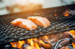 Grilled salmon steaks on a grill. Fire flame grill. Restaurant and garden kitchen. Garden party. Healthy dish. Grilled salmon steaks on a grill. Fire flame Stock Photography
