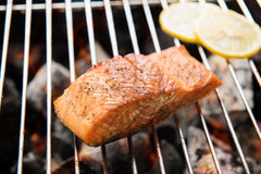 Grilled salmon steaks and lemon on the flaming Royalty Free Stock Image