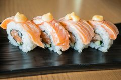 Grilled salmon sushi roll, japanese food style on black ceramic royalty free stock photos
