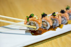 Grilled salmon sushi roll on a white plate Royalty Free Stock Images