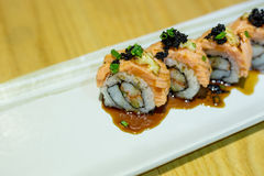 Grilled salmon sushi roll on a white plate Stock Photo