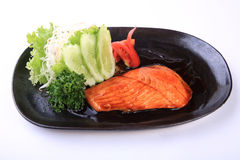 Grilled salmon teriyaki in black dish isolated on white Royalty Free Stock Images