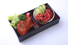 Grilled salmon teriyaki with spicy tentacles in bento isolated o Stock Image