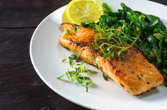 Grilled salmon with thyme, lemon and spinach on a white plate on Royalty Free Stock Images