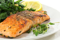 Grilled salmon with thyme, lemon and spinach on white, vegetaria Stock Photo