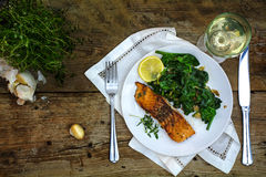 Grilled salmon with thyme, lemon, spinach and white wine on a da Stock Images