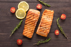 Grilled salmon and tomato, lemon, rosemary on the wooden backgro Royalty Free Stock Images