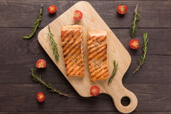 Grilled salmon and tomato, rosemary on the wooden background Stock Images