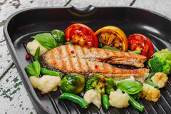 Grilled salmon. With vegetables on a grill pan stock images