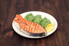 Grilled salmon with vegetables and lemon on dish Royalty Free Stock Photo