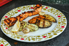 Grilled salmon. And vegetables in a plate royalty free stock photos