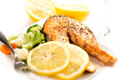 Grilled salmon and vegetables on plate with fork close up Stock Photography